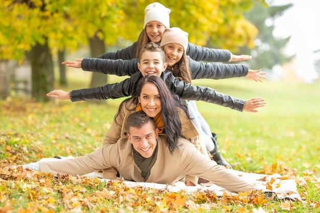 Мама, папа и трое детей с распростертыми объятиями, сложенными на улице в осенний день с разноцветными листьями.