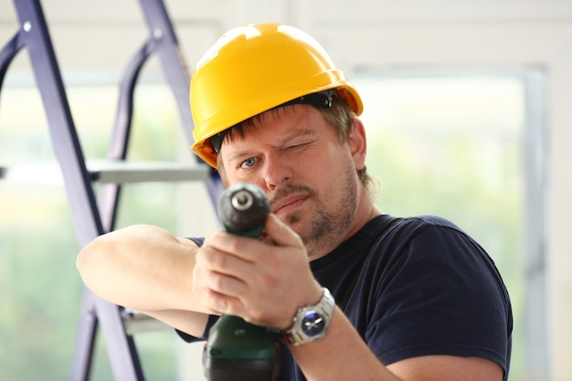 Arms of worker using electric drill closeup. manual job diy inspiration improvement fix shop yellow helmet joinery startup idea industrial education profession career concept