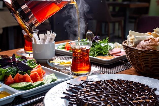 Вид сбоку наливания черного чая в стакан armudu