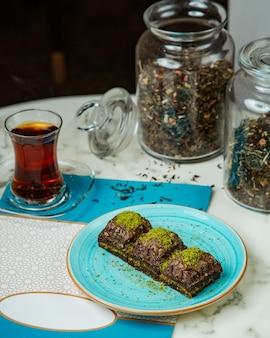 Фисташковый пахлава и черный чай в бокале armudu