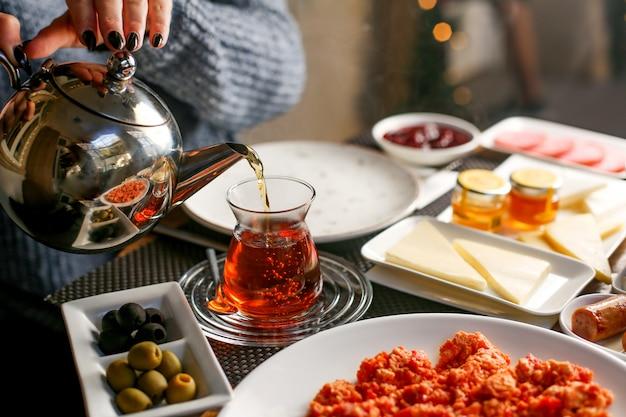 女性がarmuduグラスにお茶を注ぐ