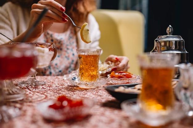 Женщина кладет ломтик лимона в чай в хрустальном бокале armudu