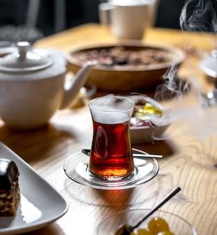 木製のテーブルにarmuduガラスの蒸気で熱いお茶の側