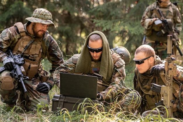 지상에 앉아서 추가 조치를 논의하는 동안 노트북을 사용하는 위장 복장의 육군 미국 군인