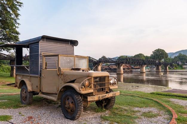 Армейский старинный автомобиль на мосту через реку квай в канчанабури
