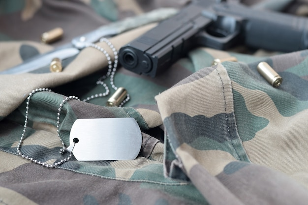 Жетон армейской собаки с 9-мм пулями и пистолетом лежит на сложенной камуфляжной зеленой ткани. набор военного ветеранов или старый дежурный трофейный набор