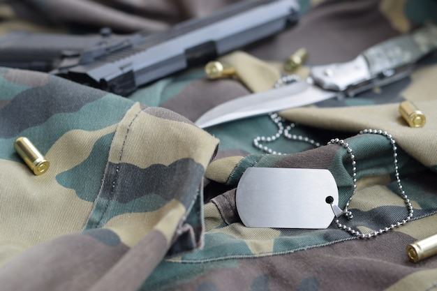 Army dog tag token with 9mm bullets and pistol lie on folded camouflage green fabric
