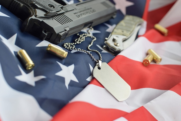 Army dog tag token with 9mm bullets and pistol lie on folded united states flag