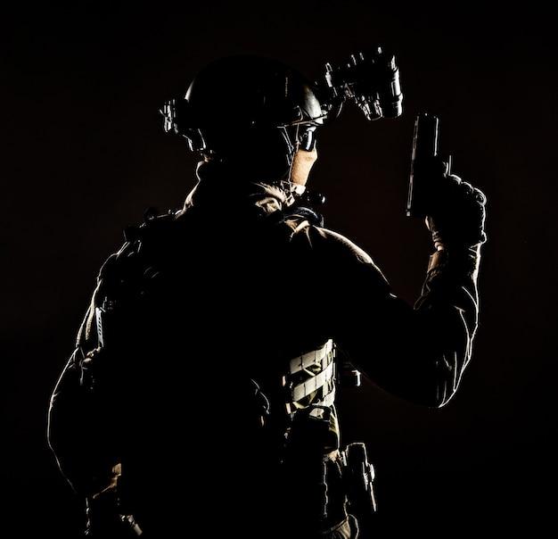 육군 엘리트 부대 군인, 경찰 특수 작전, 마스크 신원 뒤에 숨겨진 전술 탄약을 쓴 대테러 팀원, 손에 권총을 들고 뒤로 서 있는, 낮은 키 스튜디오 촬영