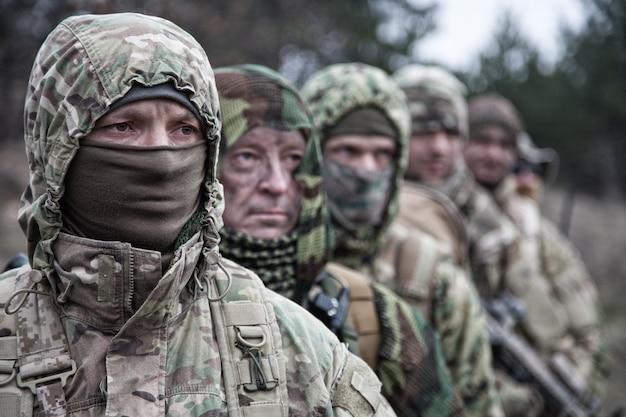 Солдаты тактической группы армейских элитных сил, опытный отряд коммандос, члены в камуфляжной форме, скрывающие лица за масками, стоящие в очереди за командиром
