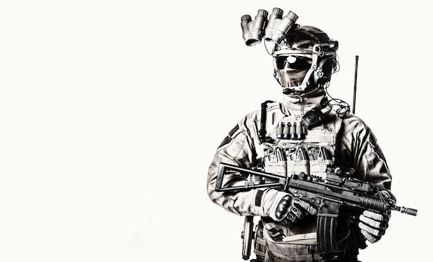 마스크와 안경 얼굴 뒤에 숨겨진 육군 엘리트 군인, 전체 전술 탄약, 장착된 야간 투시 장치, 라디오 헤드셋, 무장된 짧은 배럴 서비스 소총 스튜디오 촬영 흰색 배경