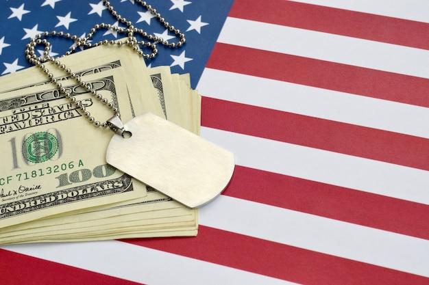 Медальоны идентификации армии и долларовых купюр на флаге соединенных штатов. военная пенсия, зарплата в армии или военная страховка