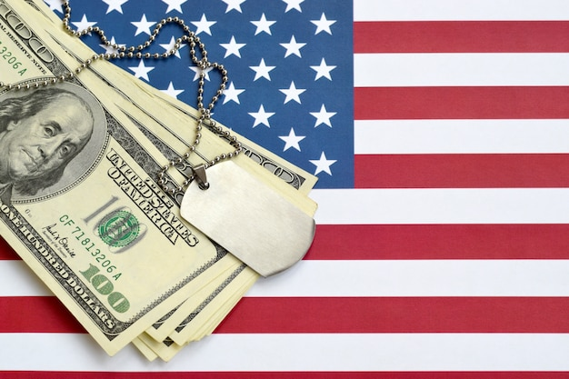 Army identification medallions and dollar bills on united states flag. military pension, salary in the army or military insurance
