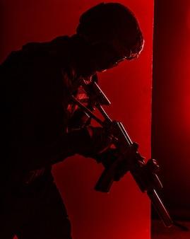 Армейская пехота, солдат сил специальных операций, боец полицейской тактической группы с глушителем в руках, крадущийся по комнате с красной сигнальной лампой, сдержанная студийная съемка с красной подсветкой