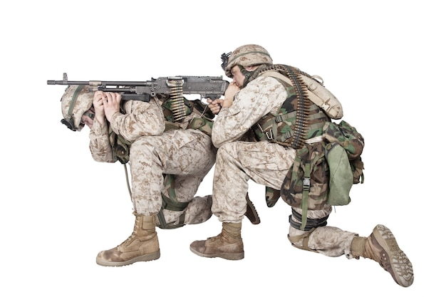 전투 위장복을 입은 육군 기관총 사수, 방탄복에 탄약 벨트가 있고, 동반자 뒤에 기관총을 얹고, 흰색 스튜디오 촬영에 격리된 적을 조준하고 쏘고 있습니다. 해병대 화력