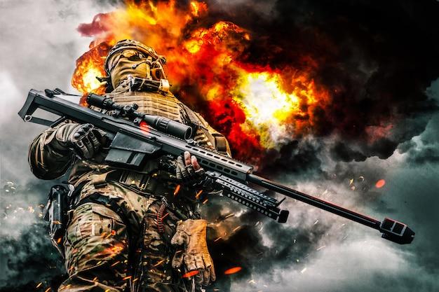 大口径のライフルでポーズをとっている特殊部隊の軍の狙撃兵。激しい爆発、火と煙が背景に渦巻く。ローアングルビュー
