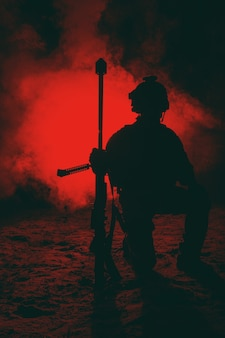 Army sniper with large caliber rifle sitting in the fire and smoke. backlit silhouette, toned image
