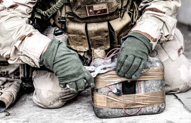 Army soldier, anti terrorist team combat engineer, ammunition technical officer, explosives military expert using pliers to cut wire on improvised explosive device, neutralizing homemade bomb on floor