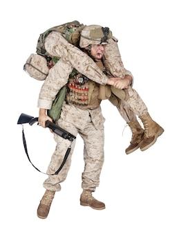 전투용 산탄총으로 무장한 육군 병사는 소방관과 함께 부상당하고 의식을 잃은 동지를 운반합니다. 군사 사상자 인명 구조, 구조 및 흰색 절연 전장에서 대피