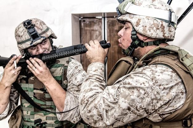 그의 동료가 총신에서 연기를 흡입하는 동안 육군 군인은 전투 산탄총 챔버에서 담배 연기를 뿜고 있습니다. 펌프액션 소총으로 마리화나를 피우는 미 해병대 보병들