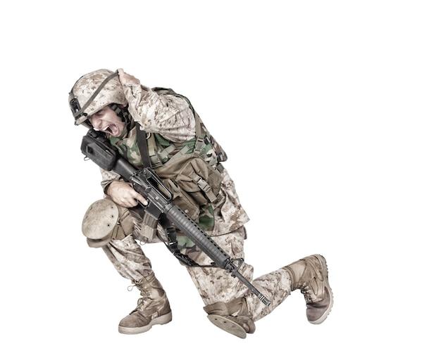 위장복을 입은 육군 군인, 돌격 소총과 기관총으로 무장하고, 땅에 웅크리고, 헬멧을 들고, 흰색 스튜디오 촬영 수류탄 또는 폭탄 폭발에 격리된 손으로 귀를 덮습니다.