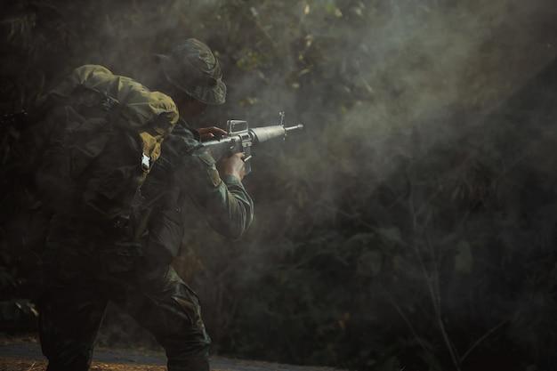 ライフルを保持している防護服の陸軍兵士。サイレンサー付きの特殊部隊兵士アサルトライフル。煙で。