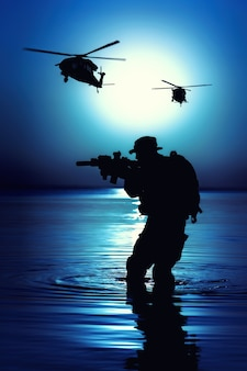 Army soldier with rifle night moon silhouette under cover of darkness in action during raid crossing river in the water. combat helicopters are supporting operation from air