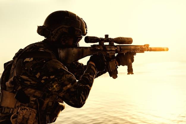 ライフルオレンジ色の夕日のシルエットと陸軍兵士