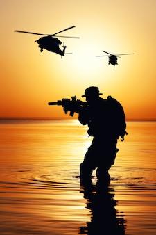 물 속에서 강을 건너는 동안 소총 일몰 실루엣이 있는 육군 군인. 공중에서 작전을 지원하는 전투 헬리콥터