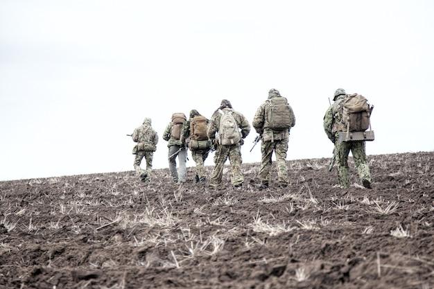 Солдаты армии на марше. группа бойцов элитных войск, тактическое подразделение коммандос, члены разведывательной группы в камуфляжной форме, идут в строю, несут рюкзаки по илистой местности
