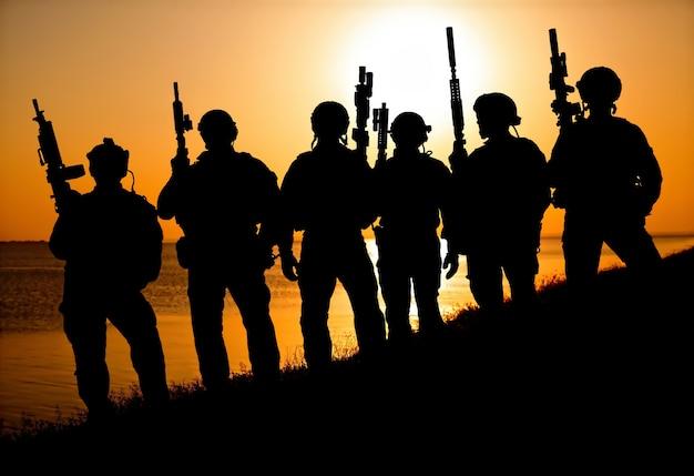 オレンジ色の夕日のシルエットのライフルを持つ陸軍兵士