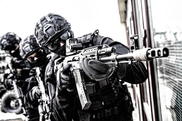 Стрелок армейского спецназа, боец полицейского антитеррористического отряда, охранник частной охранной компании в тактических боеприпасах, прицеливающихся из служебной винтовки. полицейский рейд, контртеррористическая операция, ненасыщенный