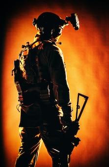 전술 탄약을 착용한 육군 특수부대 병사, 헬멧에 야간 투시경, 낮은 키에 낮은 서비스 라이플을 들고 서 있는, 백 뷰, 패브릭 배경에 빨간색 백라이트가 있는 스튜디오 촬영