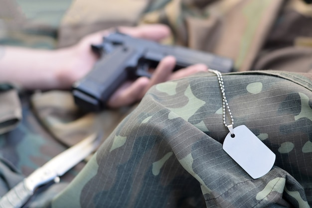 Army token lies on camouflage uniform of dead soldier and hand with pistol