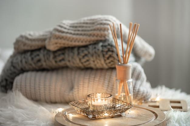 Aroma bastoncini di bambù in una bottiglia con liquido profumato con candele che restano su un vassoio di legno su sfondo sfocato.