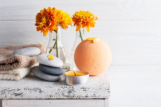 Aroma bath bomb in spa composition with orange flowers and pebbles. aromatherapy arrangement, zen still life with lit candles