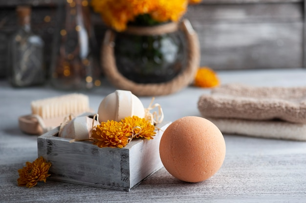 Aroma bath bombs in spa composition with orange flowers and towels