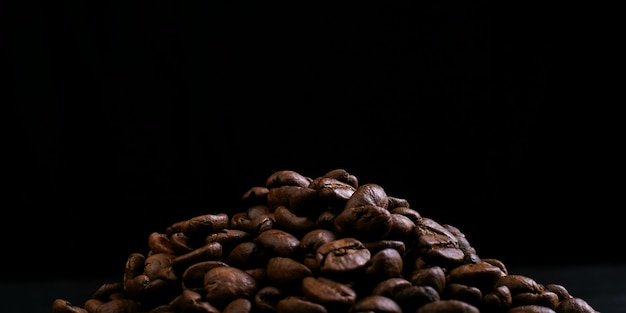 Aroma coffee beans lie crusted against a black background. copy space.