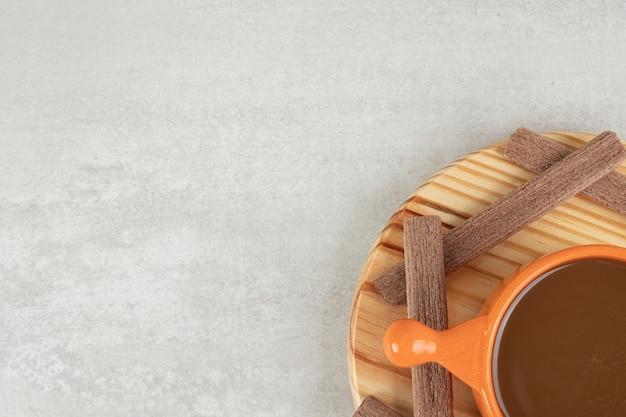 Aroma caffè e biscotti al cacao su piatto in legno