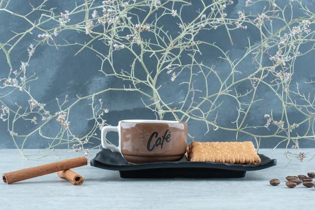 ダークプレートにシナモンスティックとクラッカーを添えたアロマコーヒー。高品質の写真