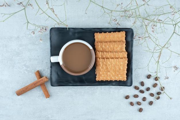 어두운 접시에 계피 스틱과 크래커를 넣은 아로마 커피. 고품질 사진