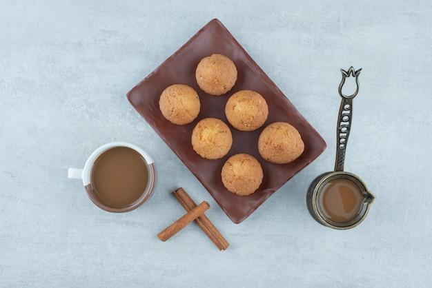 흰색 바탕에 계피 스틱과 컵케이크가 있는 아로마 커피. 고품질 사진