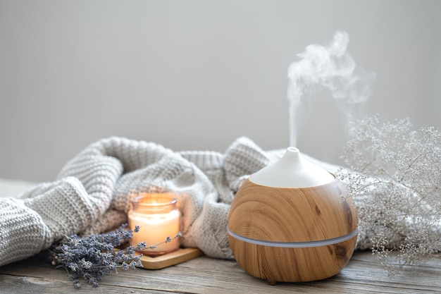 Aroma composition with a modern aroma oil diffuser on a wooden surface with a knitted element, candle and lavender.