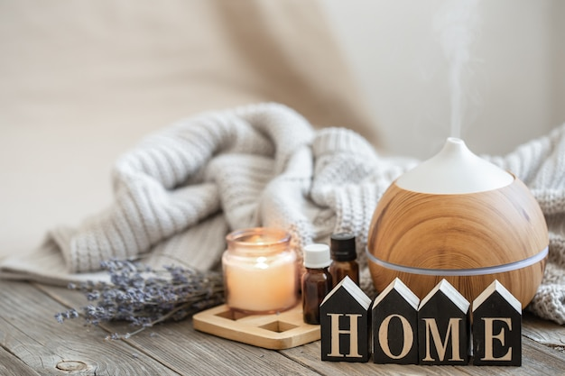 Aroma composition with modern aroma oil diffuser on wooden surface with knitted element, oils and candle on blurred background.