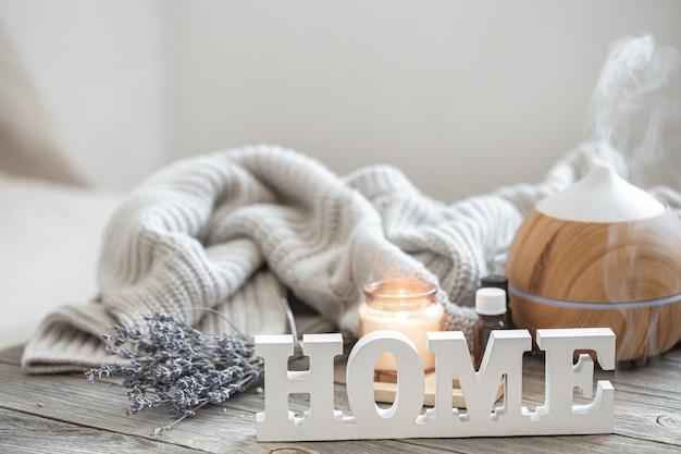 Aroma composition with modern aroma oil diffuser on wooden surface with knitted element, oils and candle on blurred background