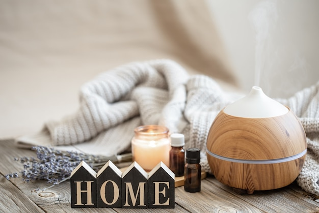 Aroma composition with modern aroma oil diffuser on wooden surface with knitted element, oils and candle