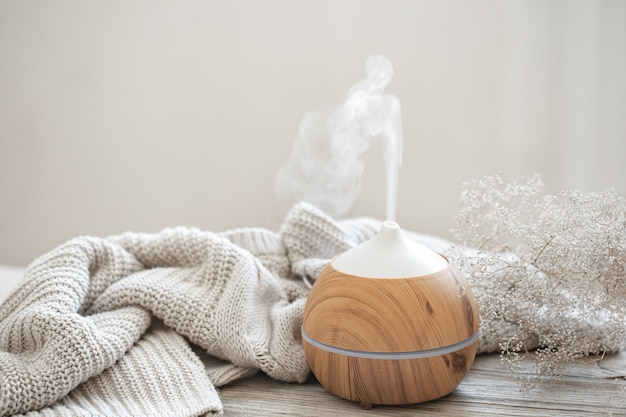 Aroma composition with a modern aroma oil diffuser on a wooden surface with a knitted element and a sprig of dried flowers.