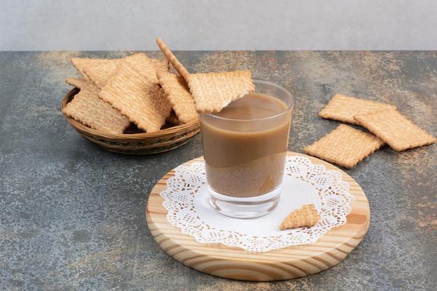 大理石の背景にクラッカーとコーヒーの香りのカップ。高品質の写真