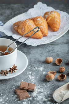 Aroma cup of tea with delicious croissants.