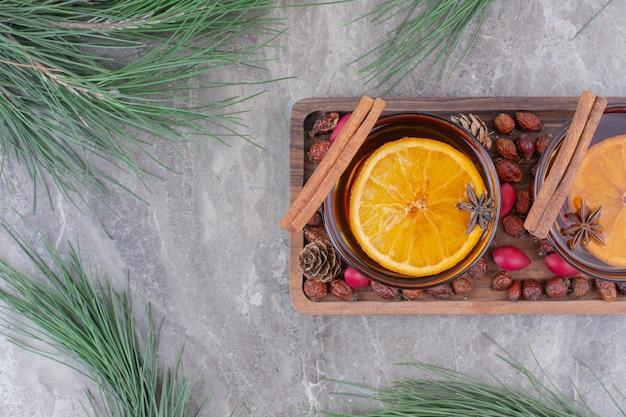 木の板にレモンとシナモンのスティックが付いたお茶のアロマカップ。